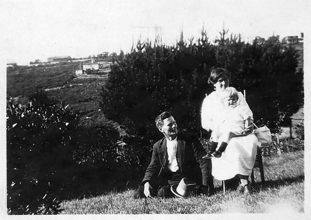 George and Kitty Cousins and baby in their garden at Blackheath